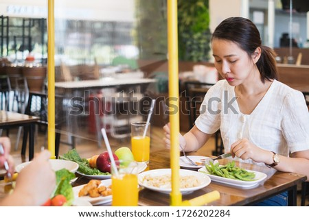 Asian woman sitting separated in restaurant eating food with table shield plastic partition to protect infection from coronavirus covid-19, restaurant and social distancing concept