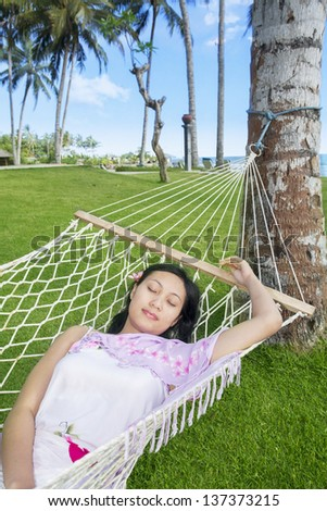 Asian woman sleep in hammock by the beach