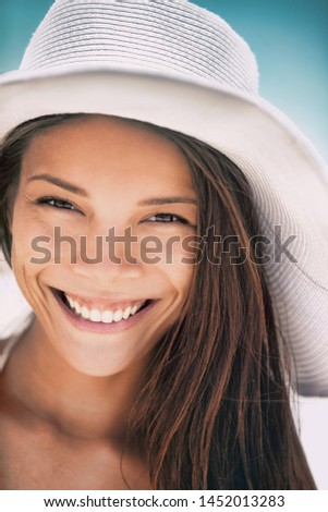 Asian woman smiling happy portrait in summer beach wearing sun hat. Beauty young girl closeup face toothy smile with perfect teeth.