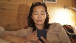 Asian woman smiling scrolling the phone. Portrait shot of woman with eyeglasses on head, sitting on a sofa with phone in hand, yellow lights of the lamp