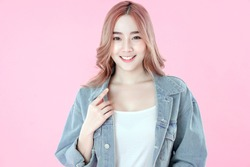 Asian woman smiling with blue jean clothing, pink background