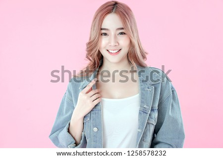 Asian woman smiling with blue jean clothing, pink background #1258578232