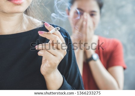 Asian woman smoking cigarette near people in family smelling pollution,passive smoking concept