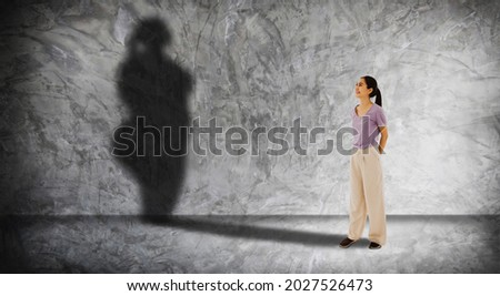 Asian woman stood looking at her own shadow on a concrete wall,imagining the future of obesity as she grew into middle age : Concept health care, nutrition, eating and obesity prevention in the future Stock foto ©