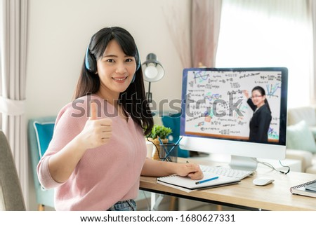 Asian woman student video conference e-learning with teacher on computer and thumb up at home. E-learning ,online ,education and internet social distancing protect from COVID-19 viruses.