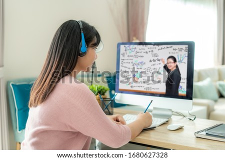 Asian woman student video conference e-learning with teacher on computer in living room at home. E-learning ,online ,education and internet social distancing protect from COVID-19 viruses.