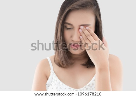 Asian woman suffering from strong eye pain against gray background. Female has a pain in the eye. Healthcare concept. Having migraine