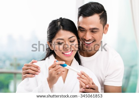 Asian woman surprising her husband with positive pregnancy test, he seems reasonably pleased