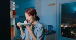 asian woman takes cake from opened refrigerator for late night supper in kitchen at night