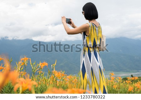 asian woman taking a picture and stand at the yellow tiger lily farm