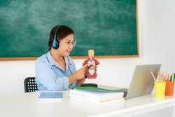 Asian woman teacher teaching physiology science via video conference e-learning in laptop with blackboard at classroom. Homeschooling and distance learning ,online ,education and internet.