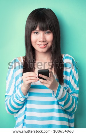 Asian Woman texting on her cell phone leaning against a green wall.