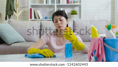 asian woman tidy up a house. young housewife is wiping dust using a spray and fabric while cleaning seriously on the table with a boring upset face. Neat and clean housekeeping concept. #1242602443