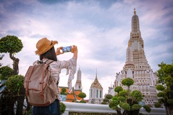 Asian woman tourists are taking photos With a smartphone at the Wat Arun temple on vacation Bangkok Thailand.