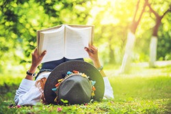 Asian woman travel nature. Travel relax. sleep Reading book On the lawn in the park. in summer.