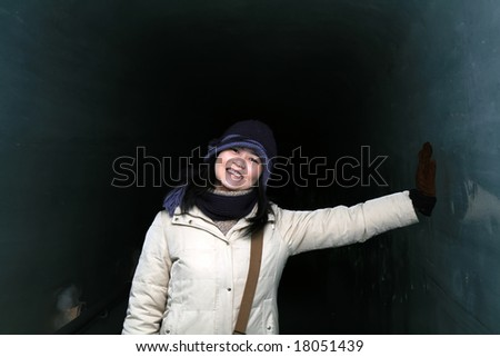 Asian woman traveler having fun inside an ice tunnel during winter.