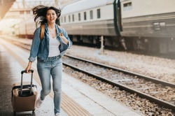 Asian Woman traveler tourist running with luggage at train station. Active and travel lifestyle concept