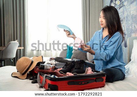 Asian woman traveller select her face mask for travel today in hotel room with travel bag for prevent corona virus covid19, this image can use for new normal, covid-19, covid and travel concept
