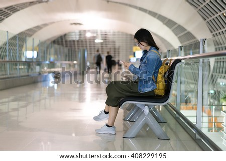 Asian woman traveller using smart phone, waiting for boarding at the airport's terminal