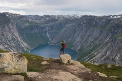 Asian woman traveller with backpack standing on rock and enjoying landscape of mountains and lake in Trolltunga mountain cliff trail, Odda town, Norway, Scandinavia, Europe