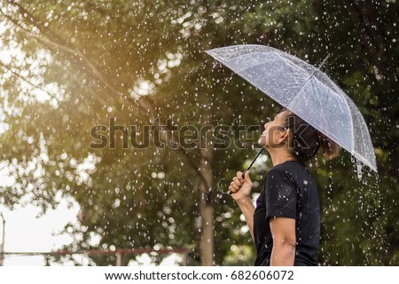 Asian woman under an umbrella in the rain. #682606072