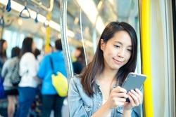 Asian woman use of mobile phone in Hong Kong metro