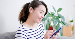 asian woman use wireless earbuds to listen music at home
