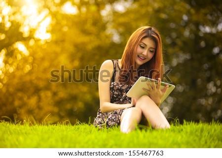 Asian woman using digital tablet in park, Outdoor Portrait