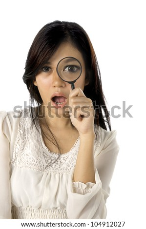 Asian woman using magnifier on her eye isolated over white background