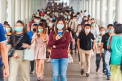 Asian woman using mobile phone between Crowd of blurred unrecognizable business people wearing surgical mask for prevent coronavirus Outbreak in rush hour working day at Bangkok transportation