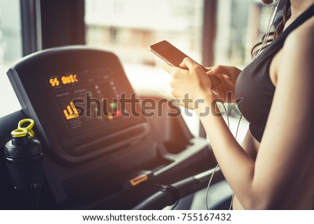 Asian woman using smart phone when workout or strength training at fitness gym on treadmill. Relax and Technology concept. Sports Exercise and Health care theme. Happy and Comfortable mood.