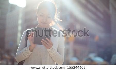 Asian woman using tablet pc computer outdoor on a city street