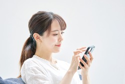Asian woman using the smart phone on the sofa
