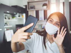 Asian woman video calling with smartphone at home, meeting online by app, social distancing, work from home, Stop the spread of the coronavirus or covid-19 concept.