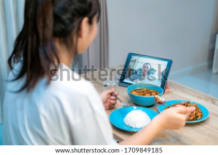 Asian woman virtual happy hour meeting dinner and eating food online together with her boyfriend in video conference with tablet for a online meeting in video call for social distancing