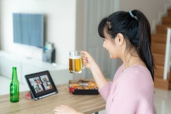 Asian woman virtual happy hour meeting party and drinking alcohol beer online together with her friend in video conference with digital tablet for a online meeting in video call for social distancing