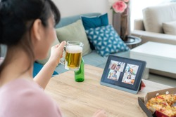 Asian woman virtual happy hour meeting party and drinking alcohol beer online together with her friend in video conference with digital tablet for a online meeting in video call