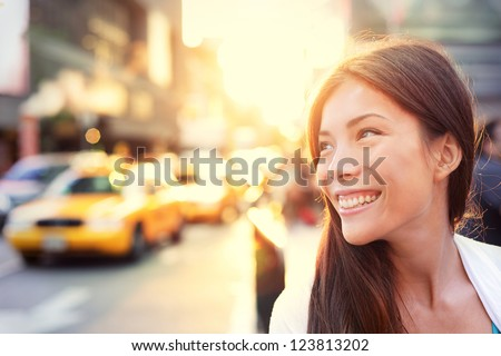 Asian woman Vivacious in New York City with a beautiful beaming smile backlit by the warm glow of the sun shining down a busy street with taxicabs in downtown Manhattan, New York City.