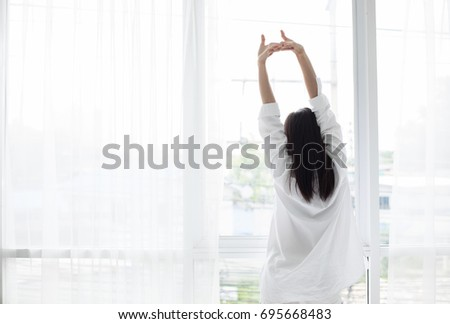 Asian woman waking up in her bed fully rested and open the curtains in the morning to get fresh air. #695668483