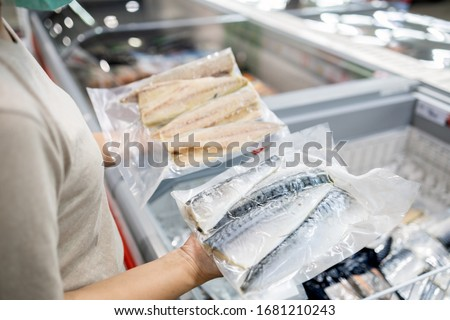 Asian woman wear face mask,choosing packed frozen cut fish in freezer in food department of supermarket,people panic buying, hoarding during the Covid-19,Coronavirus spread,girl preparing for pandemic