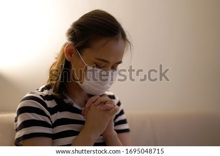 Asian woman wear face mask for protection from air pollution or coronavirus praying  by faith, Hands folded in prayer with copy space concept for faith, spirituality and religion.