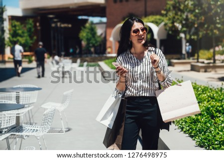 92fafd9e38b asian woman wear sunglasses in bargain summer sale joyfully buying in clothes  store. Happy young