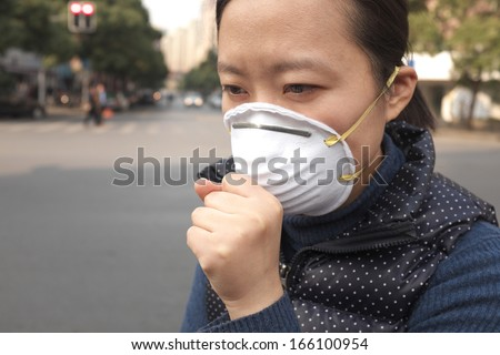 Asian woman wearing a protective face mask on a city street with air pollution