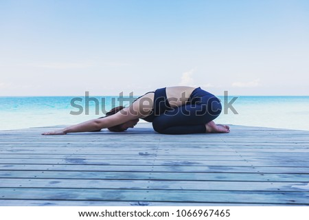 Asian woman wearing black sportswear relaxing in yoga Child's Pose stretching exercises muscle for warm up on beach in Maldives with seaside,Feeling so comfortable and relax in holiday,Healthy Concept