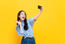 Asian woman wearing casual jean clothes taking selfie and waving hand to smartphone isolated on yellow background.