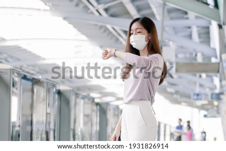 Asian woman wearing face mask and dressing casual business, looking on her watch, waiting for a train while standing on railway station and going to work. New Normal, Social Distancing Concept. Stockfoto ©