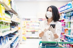 Asian woman wearing face mask and rubber glove push shopping cart in supermarket departmentstore. Girl hold smartphone choose & look grocery things to buy during coronavirus crisis, covid19 outbreak.