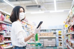 Asian woman wearing face mask and rubber glove push shopping cart in suppermarket departmentstore. Girl hold smartphone choose & look grocery things to buy during coronavirus crisis, covid19 outbreak.