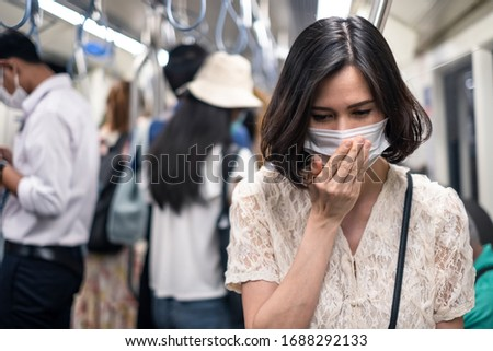Asian woman wearing mask for prevent dusk pm 2.5 bad air pollution and coronavirus or covid-19 having a dry cough. Girl wears mask due to bad smell and prevent virus infection from people in train.