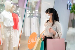 Asian woman wearing mask over her face looking new collection dress at shopping mall with shopping bag for healthcare and prevention from coronavirus, Covid19 influenza in crowded place.
